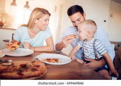 Portrait of happy family eating pizza in living room,enjoying in dinner.