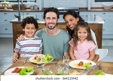Portrait of happy family eating together in the kitchen