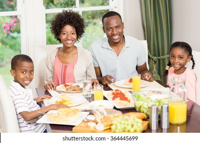 Portrait of happy family eating together at home