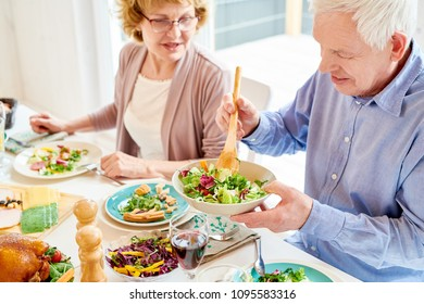 Portrait of happy family enjoying dinner sitting round festive table with delicious dishes, focus two grandparents serving food during holiday celebration in modern sunlit apartment, copy space