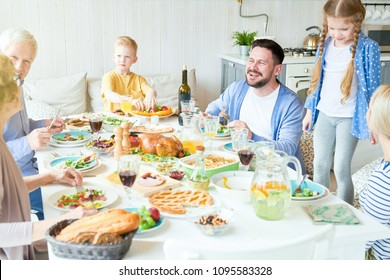Portrait of happy family enjoying dinner together sitting round festive table with delicious dishes, focus on laughing man talking to relatives during  holiday  celebration in modern sunlit apartment