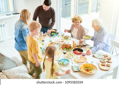 Portrait of happy family enjoying dinner together sitting at table with delicious dishes, focus two grandparents smiling happily during holiday celebration in modern sunlit apartment, copy space