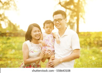 Portrait of happy family enjoying outdoor activity together, walking on garden park in beautiful sunset during holiday vacations.