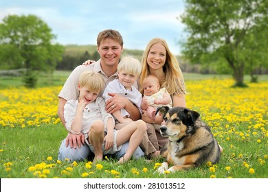 A portrait of a happy family of five caucasian people, including big brother, toddler boy, and baby sister are relaxing in a yellow Dandelion flower meadow with their pet dog.
