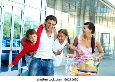 Portrait of happy family of four with cart of foodstuff