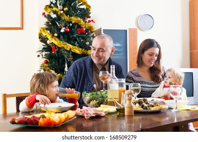 Portrait of Happy family of four celebrating Christmas  over holiday table at home interior
