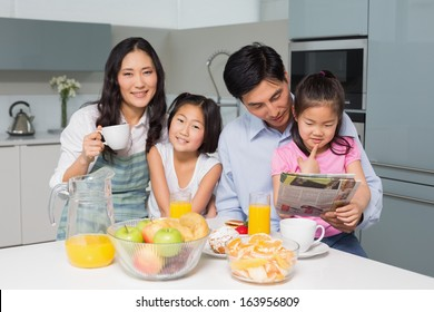 Portrait of a happy family of four enjoying healthy breakfast in the kitchen at home