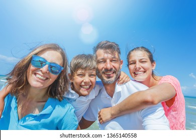 Portrait of Happy family of four having fun at beach together. Fun happy lifestyle in the summer leisure