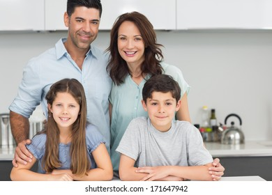Portrait of a happy family of four in the kitchen at home
