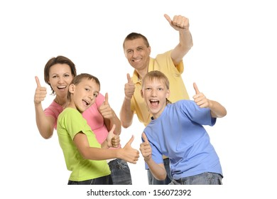 Portrait of happy family of four on a white background showing thumbs up
