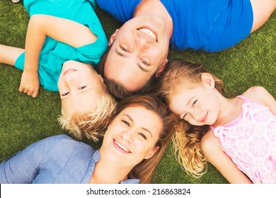Portrait of Happy Family of Four Outside On the Grass