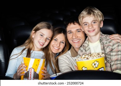 Portrait of happy family of four with popcorn at cinema theater