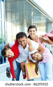 Portrait of happy family of four with shopping bags having fun