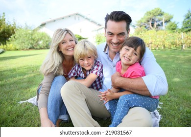 Portrait of happy family of four sitting in yard