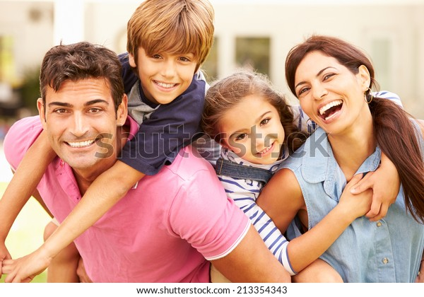 Portrait Of Happy Family In Garden At Home
