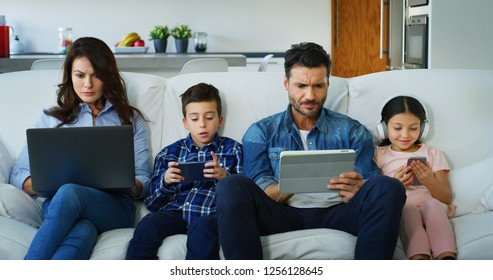Portrait of happy family having fun using different modern media devices on sofa in living room in slow motion. Concept of  family entertainment, education, technology