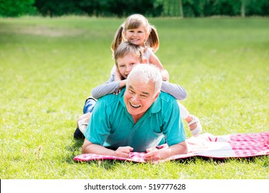 Portrait Of Happy Family Having Fun Lying On Green Grass Together In Park