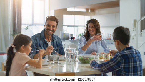 Portrait of happy family having lunch in dining room. Concept of healthy food, wellbeing, happy family