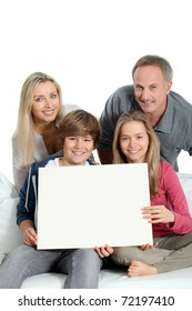 Portrait of happy family holding white message board