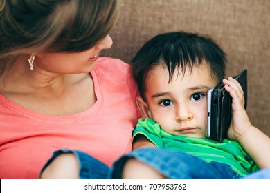Portrait of a happy family at home, mom holding on hands a sleepy child who leaned his cell phone to his ear with interest, The parent lovingly looks at son