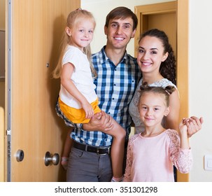 Portrait happy family with little children holding keys of new apartment