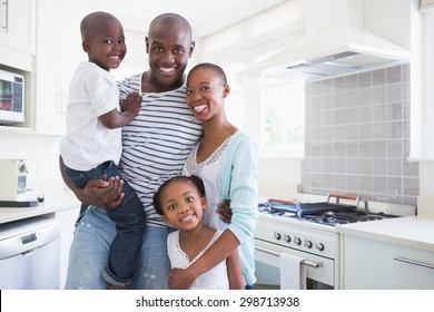 Portrait of a happy family looking at the camera in the kitchen