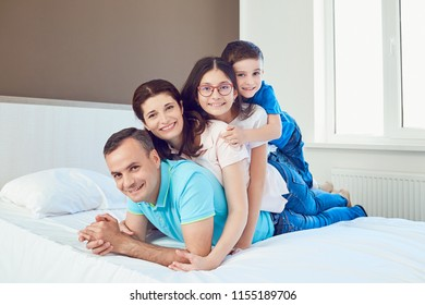 Portrait of happy family lying in bedroom