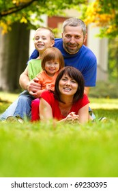 A portrait of a happy family lying on the grass in a park.