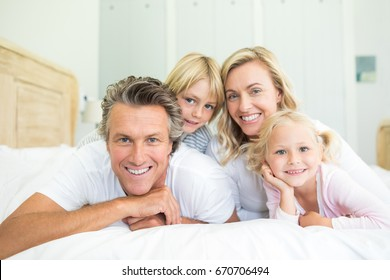 Portrait of happy family lying together on bed in bedroom