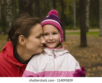 portrait of happy family mother with daughter in park