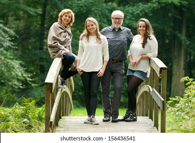 Portrait of a happy family with mother father and daughters standing on bridge in the forest