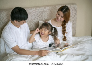 Portrait of happy family with mother, father and daughter in bed , read book in bed