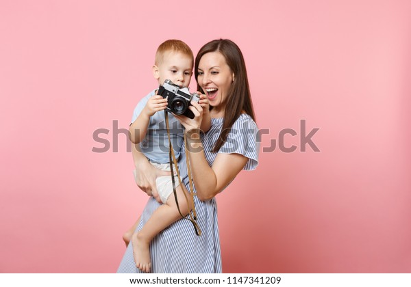 Portrait of happy family. Mother keep in arms, have fun, hug son baby boy, take picture on retro vintage photo camera on pink background. Sincere emotions, Mother's Day, parenthood, childhood concept