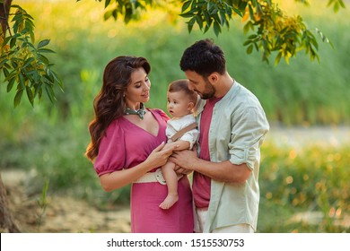 Portrait of a happy family on a walk mom dad and little son in the summer on the river bank.