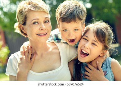 portrait of a happy family outdoors. mom with children in the summer. Mother and kids