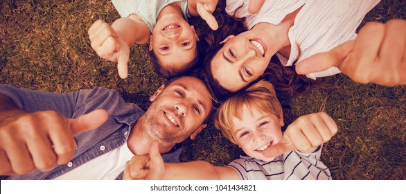 Portrait of happy family in park together gesturing thumbs up