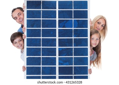 Portrait Of A Happy Family Peeping From Solar Panel Against White Background