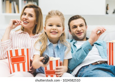 portrait of happy family with popcorn watching film together at home