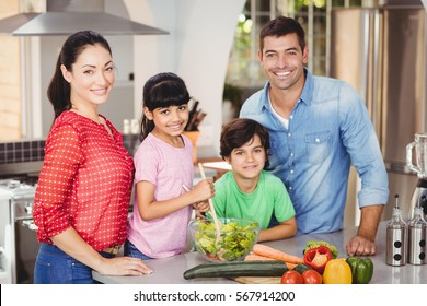Portrait of happy family preparing salad while standing at home