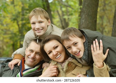 Portrait of happy family relaxing in autumn park