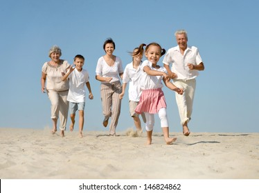 portrait of a happy family running barefoot in the sand in the summer