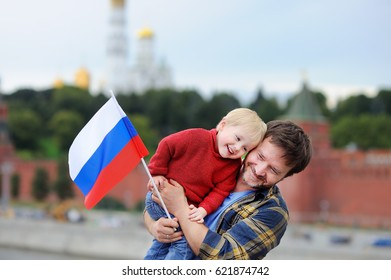 Portrait of happy family with russian flag with Moscow Kremlin on background