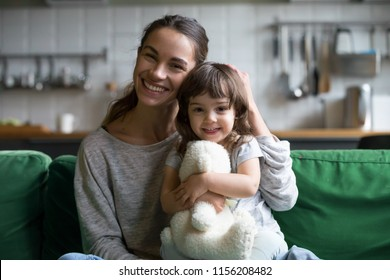 Portrait of happy family single mother and kid daughter embracing on sofa at home, young cheerful mom sister stroking cute girl hugging looking at camera, mum and child sincere relationship concept