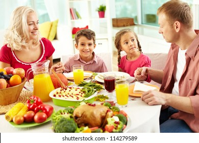 Portrait of happy family sitting at festive table and holding each other by hands before praying