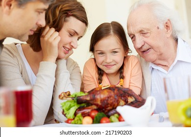 Portrait of happy family sitting at festive table and looking forwards to eating tasty turkey