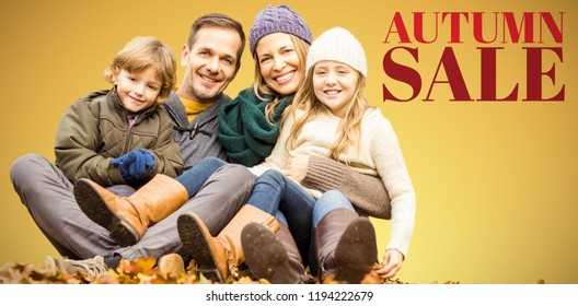 Portrait of happy family sitting on field at park against abstract yellow background