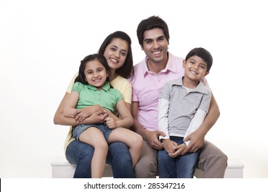 Portrait of a happy family sitting on bench over white background
