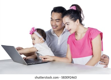 Portrait of happy family sitting on the chair while using laptop together, isolated on white background