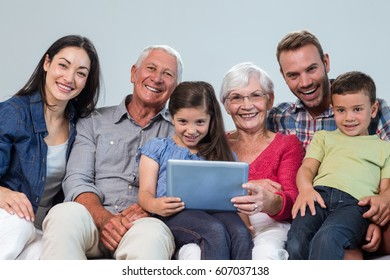 Portrait of happy family sitting on sofa using a digital tablet in living room