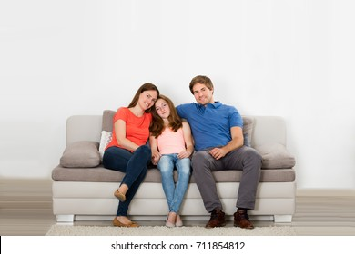 Portrait Of Happy Family Sitting On Couch In Living Room